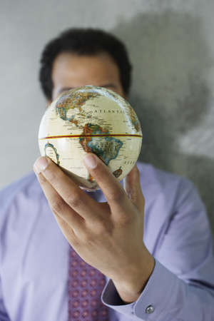 African American businessman holding globe in front of face Stock Photo - 16091222