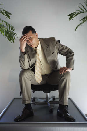 wearying: African American businessman sitting in chair on pedestal