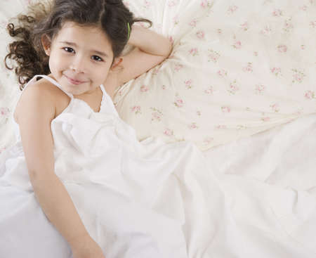 bedcover: Young Hispanic girl in bed LANG_EVOIMAGES