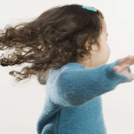 lighthearted: Young Hispanic girl spinning around LANG_EVOIMAGES