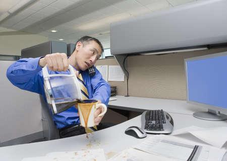 endangering: Asian businessman spilling coffee on desk