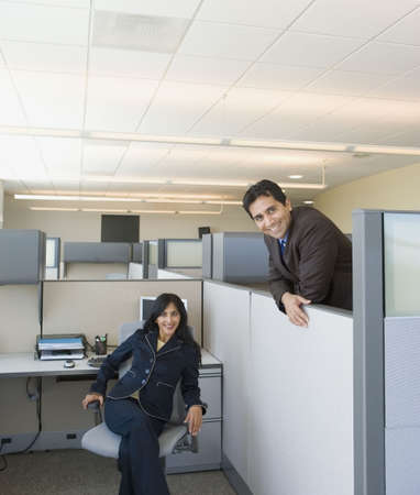 office furniture: Two coworkers in office cubicles LANG_EVOIMAGES