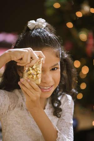 christmas gift: Hispanic girl holding Christmas gift in front of face