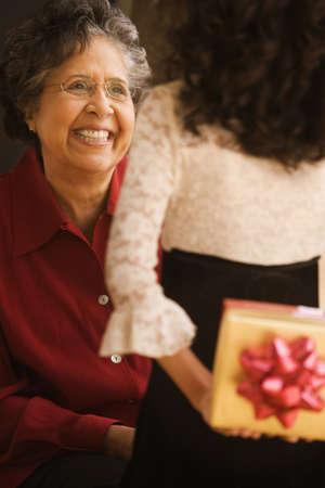 Hispanic granddaughter giving grandmother gift Stock Photo - 16091272