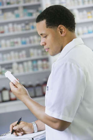 one mid adult man only: African American male pharmacist with prescription bottle LANG_EVOIMAGES