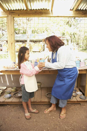 gramma: Hispanic woman and girl in pottery shop LANG_EVOIMAGES