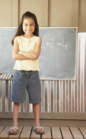 Hispanic girl standing in front of blackboard LANG_EVOIMAGES