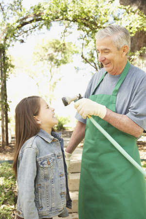 mischeif: Hispanic grandfather and granddaughter playing with hose LANG_EVOIMAGES
