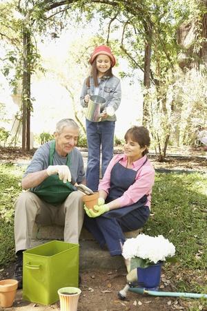 mischeif: Hispanic grandparents and granddaughter gardening
