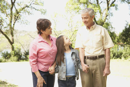 Hispanic grandparents and granddaughter holding hands outdoors Stock Photo - 16091303