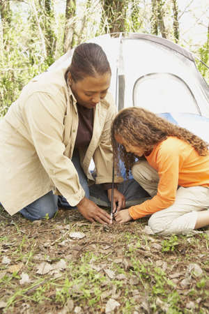 babyboomer: African American mother and daughter setting up tent