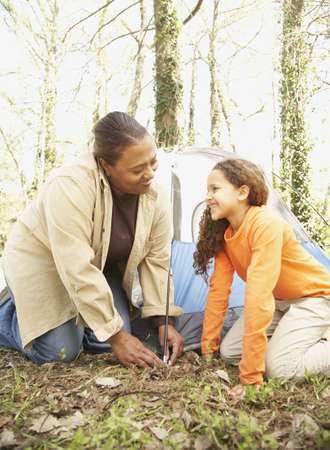 cooperating: African American mother and daughter setting up tent