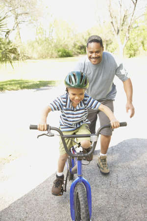 African American father helping son ride bicycle