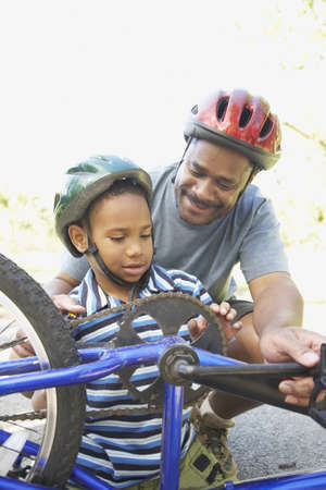 African American father helping son fix bicycle LANG_EVOIMAGES
