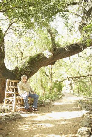 Senior Hispanic man sitting on bench in park Stock Photo - 16091319