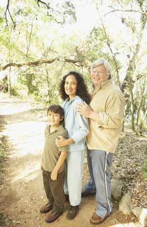 fathering: Hispanic grandparents with grandson on nature trail