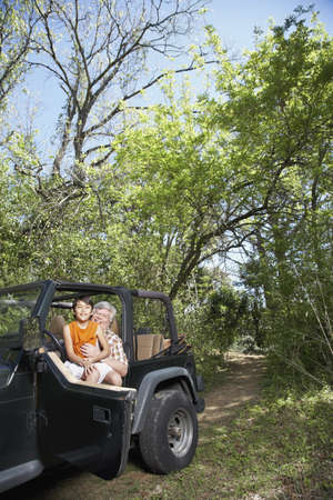 babyboomer: Hispanic grandfather with grandson in jeep LANG_EVOIMAGES