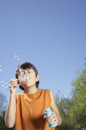 poppa: Hispanic boy blowing bubbles outdoors