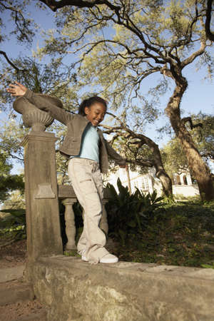 jeopardizing: African American girl balancing on wall LANG_EVOIMAGES