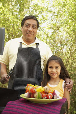 grill: Hispanic father and daughter next to barbecue grill with kebabs