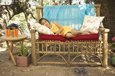 Hispanic girl laying on bench outdoors Stock Photo - 16091338