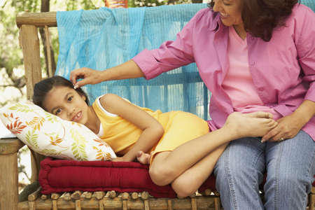 gramma: Hispanic mother and daughter on bench outdoors LANG_EVOIMAGES
