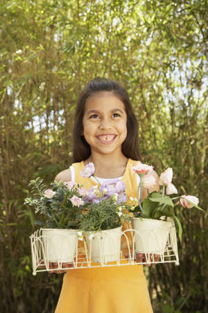 Hispanic girl holding potted flowers outdoors Stock Photo - 16091357