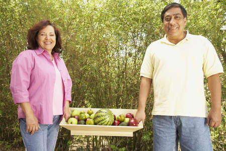 Hispanic couple carrying tray of fruit outdoors Stock Photo - 16091361