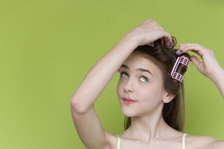 Studio shot of young girl with curlers  Imagens