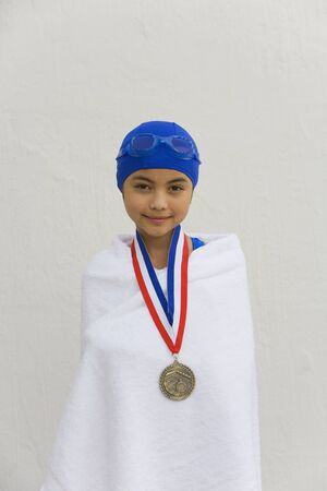 prevailing: Hispanic girl wrapped in towel with swimming metal LANG_EVOIMAGES
