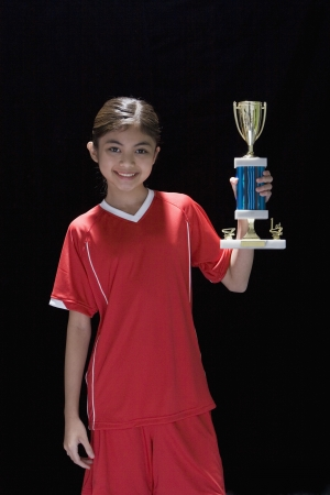 Studio shot of young Hispanic girl with soccer trophy 스톡 콘텐츠