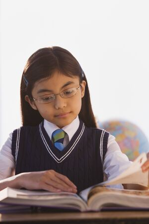 Young Hispanic girl reading book in classroom Standard-Bild