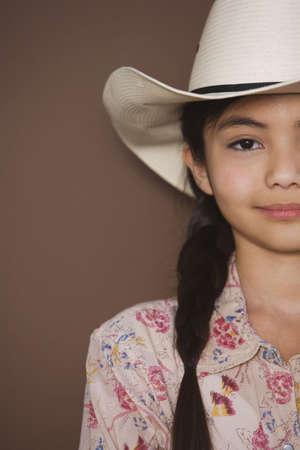 Studio shot of young girl wearing cowboy hat