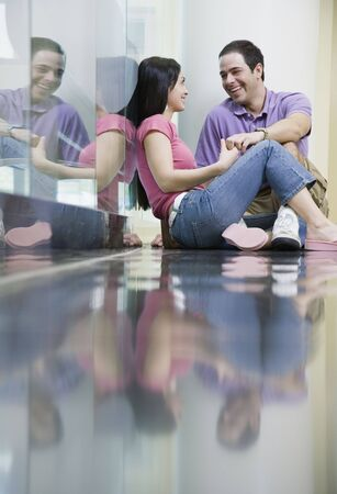 courting: Couple sitting on reflective floor holding hands LANG_EVOIMAGES