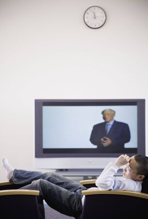 wearying: Young Asian man in chair next to television