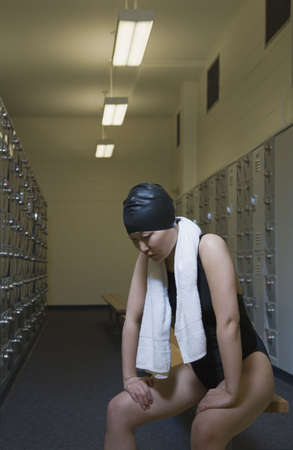 wearying: Female Asian swimmer with towel in locker room LANG_EVOIMAGES
