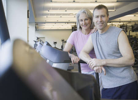 feeling up: Couple standing on treadmill at gym