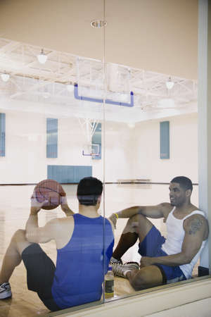 north western european descent: Two men sitting on basketball court LANG_EVOIMAGES