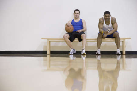 north western european descent: Two men sitting on sidelines of basketball court LANG_EVOIMAGES