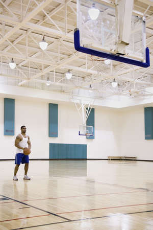 longshot: Man with basketball on court