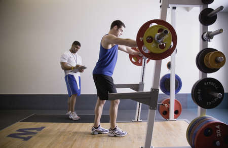 north western european descent: Male personal trainer with male client lifting weights