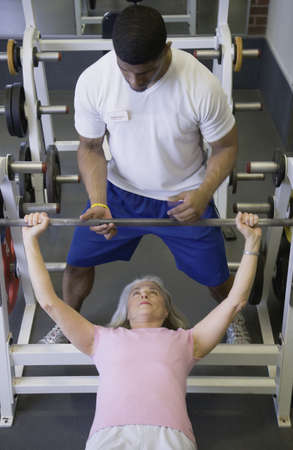 Male personal trainer with female client lifting weights Stock Photo - 16091468