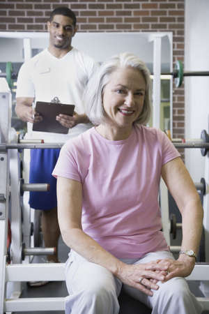 Male personal trainer with female client at gym Stock Photo - 16091469