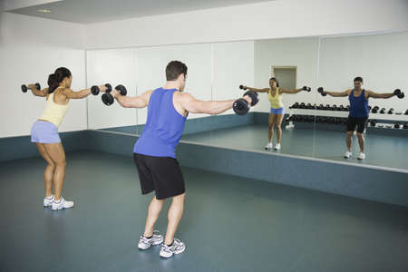 north western european descent: Man and woman lifting weights at gym LANG_EVOIMAGES