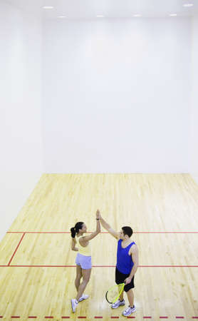 longshot: Man and woman high fiving on Squash court LANG_EVOIMAGES