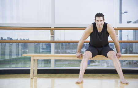 athletic gear: Man in athletic gear sitting in dance studio