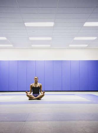 longshot: Woman meditating indoors LANG_EVOIMAGES