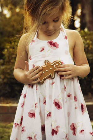 Girl holding gingerbread man outdoors Stock Photo - 16091501