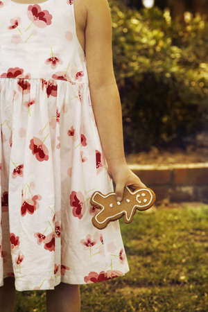 Girl holding gingerbread man outdoors Stock Photo - 16091504