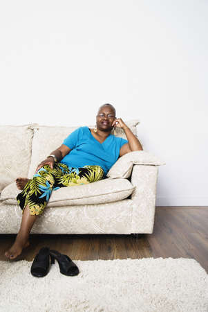 davenport: Middle-aged African woman sitting on sofa